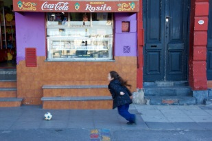 Kid playing with ball in La Boca, Buenos Aires.